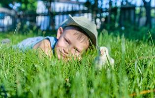Young Boy Lying in Long Grass with Fuzzy Chick