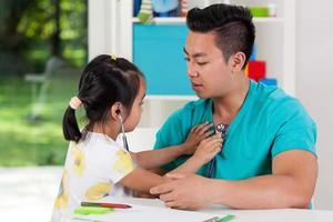 chica asiática examinando a su papá