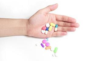 mão segure muitos remédios, caixas de remédios ao fundo