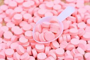 muitas pílulas cor de rosa com colher para o conceito de cuidados de saúde