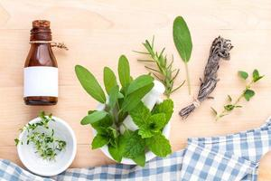 Alternative health care fresh herbal in white mortar on wooden.