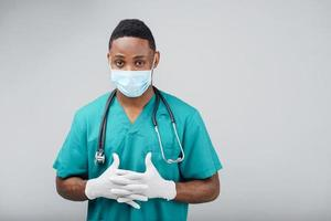 Thoughtful african american doctor holding hand in blue uniform photo