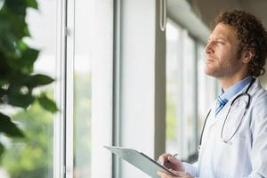 Thoughtful doctor with clipboard