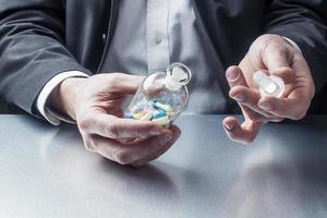 zakenman het openen van een pot vol pillen