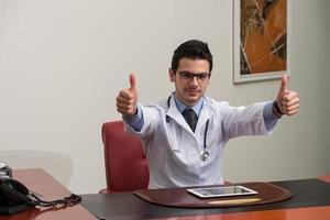 Doctor mostrando signo bien con su pulgar arriba foto