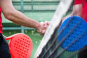 Friends shaking hands in paddle tennis field photo