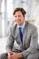 Retrato vertical del empresario corporativo sentado foto