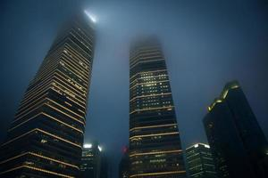 Corporate buildings in fog at night photo