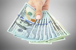 Hand holding money - United States dollar (USD) bills photo