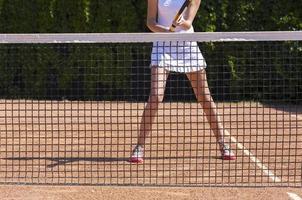 Slim legs of female tennis athlete behind fishnet barrier photo
