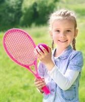 adorável menina sorridente com raquete e bola
