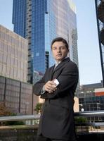 corporate portrait attractive businessman standing outdoors urban office buildings photo
