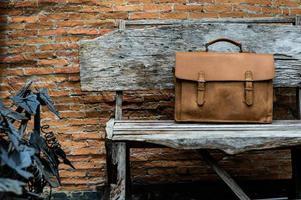 Bolso para portátil de cuero marrón corporativo en silla de madera vieja foto