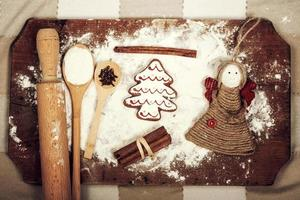 Christmas cookies, spices and flour on wooden chopping board