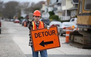 trabajador de la construcción con cartel de desvío foto