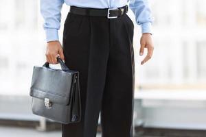 agradable hombre de negocios de pie cerca de la oficina foto