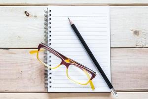 cuaderno, lápiz y anteojos en mesa de madera