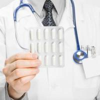 Doctor holdling pills in hand - heath care concept