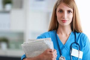 Portrait of woman doctor with folder at hospital corridor photo
