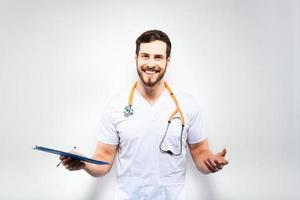 Handsome doctor standing next to wall photo