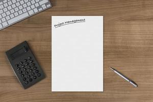 gestione del progetto del foglio bianco su una tavola di legno con il calcolatore