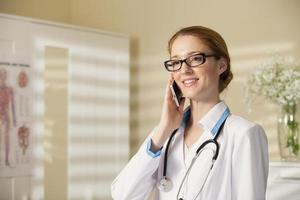 Young beautiful woman doctor with phone