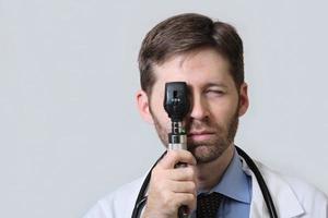 médico con barba utilizando oftalmoscopio