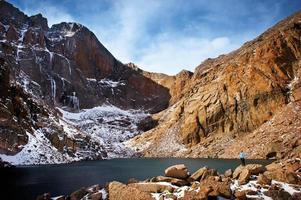 excursionista examina el lago abismo