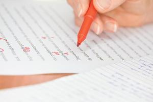 Hand with Red Pen Transcribing a Story photo