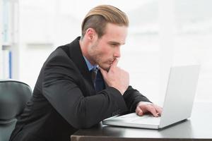 Focused businessman in suit using laptop photo