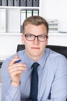joven empresario está sosteniendo una pluma en la mano foto