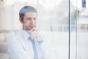 lachende zakenman kijkt uit het raam