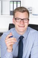 jeune homme d'affaires tient un stylo à la main