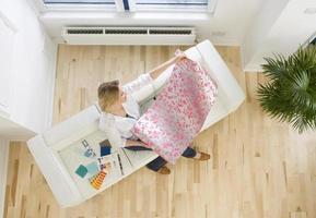 mulher no sofá, olhando para a amostra de papel de parede
