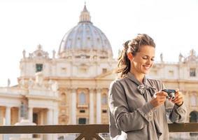Woman checking photos in camera near basilica di san pietro