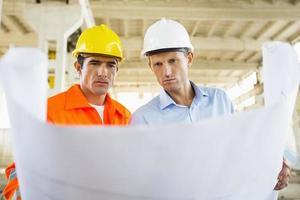 arquitectos varones revisando planos en el sitio de construcción foto