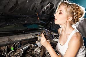 Girl checks the oil level in the car
