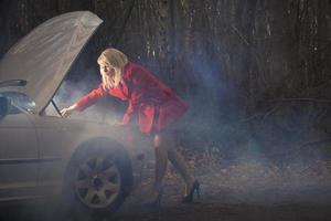 mulher olhando sob o capô do carro à noite