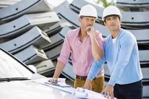 arquitectos con planos en el sitio de inspección de automóviles foto