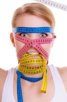 obsesionada mujer en forma con cintas métricas. tiempo para adelgazar dieta.