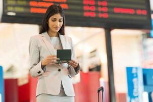 young indian businesswoman looking at air ticket photo