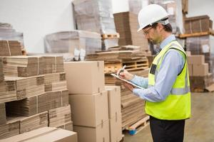 Warehouse worker checking his list on clipboard