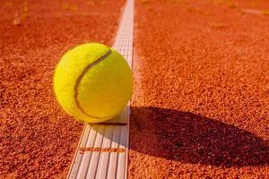 pelota de tenis amarilla tocando la línea foto