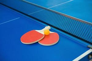 raquetas de ping-pong y pelota y red en la mesa de ping-pong azul
