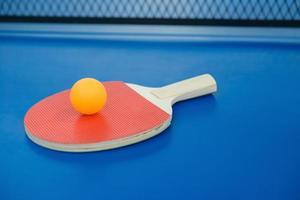 raqueta de ping-pong y pelota sobre una mesa de ping-pong azul