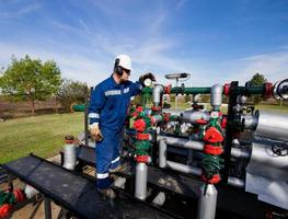 A worker monitoring a meter attached to a system of pipes photo