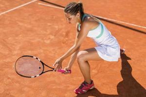 mujer joven jugando tenis foto