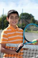 Boy holding tennis ball and racket