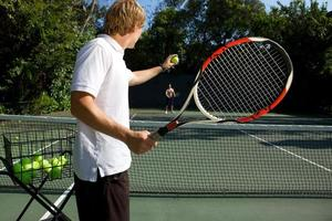 A tennis instructor about to serve a ball to a student
