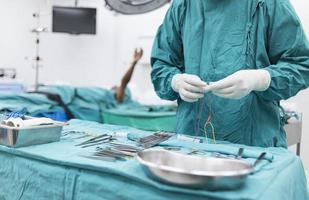scrub nurse preparing medical instruments for operation photo